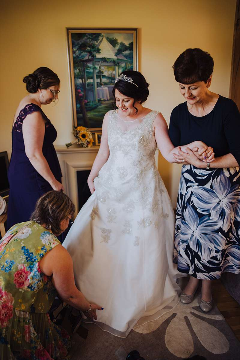 friends and family with the bride getting ready bespoke bridal gown